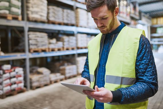 Ondernemer bekijkt in magazijn op zijn tablet het voorraadbeheerstysteem