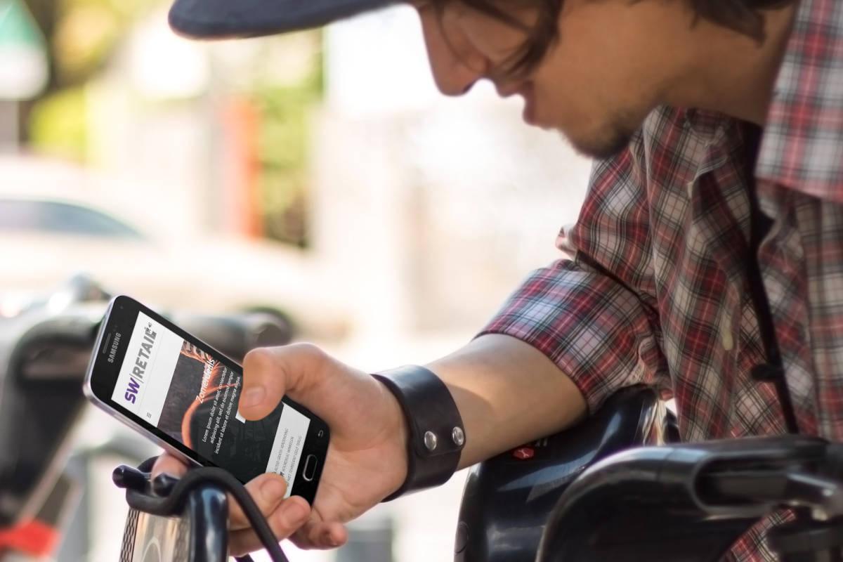 Toerist op publieke fiets bekijkt voorbeeld webshop op mobiel