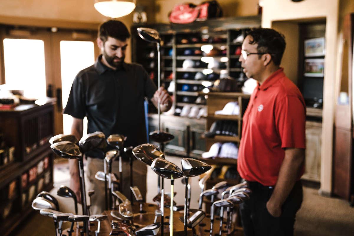 Medewerker en klant in sportwinkel voor golf