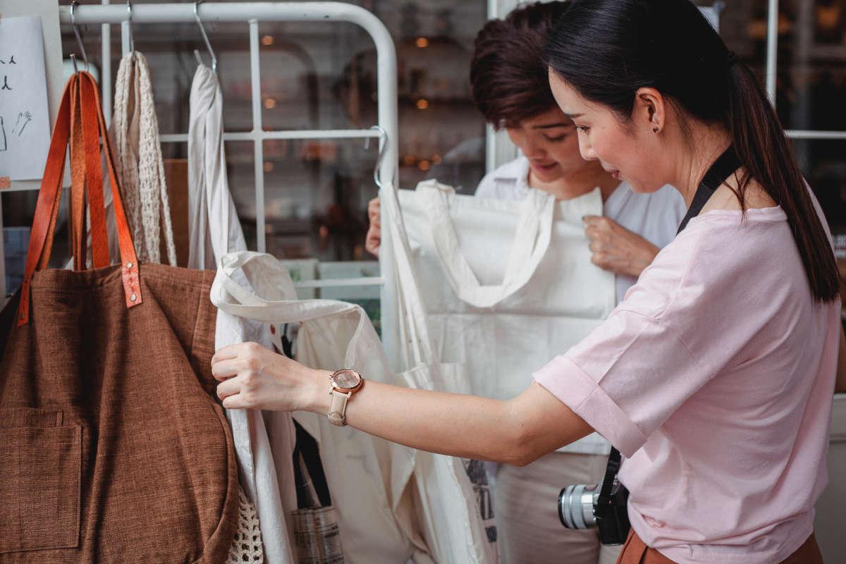 Twee toeristen bekijken draagtassen in toeristenwinkel