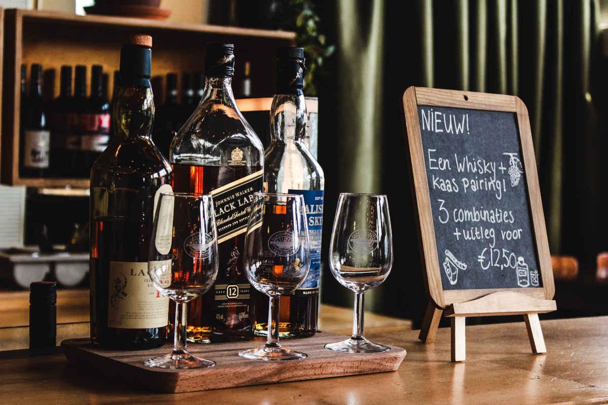 Plankje met sterke drank en bijbehorende glazen en een krijtbord met begeleidende tekst