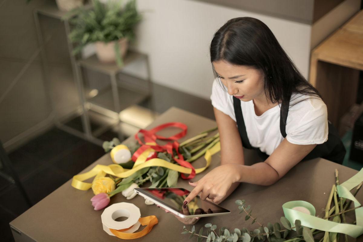 Medewerker in huis & tuinwinkel aan het werk met kassasysteem op tablet