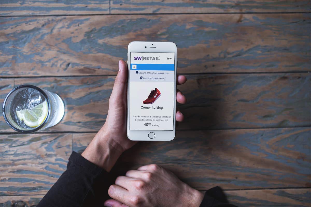 Bovenaanzicht mobiel met voorbeeld sportwebshop in handen en glas water op tafel