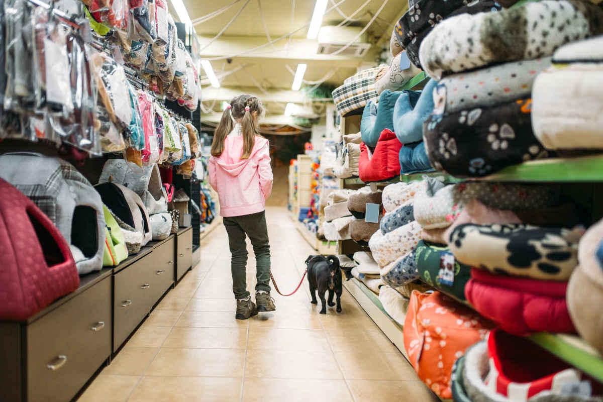 Meisje en hond lopen door gangpad in dierenwinkel