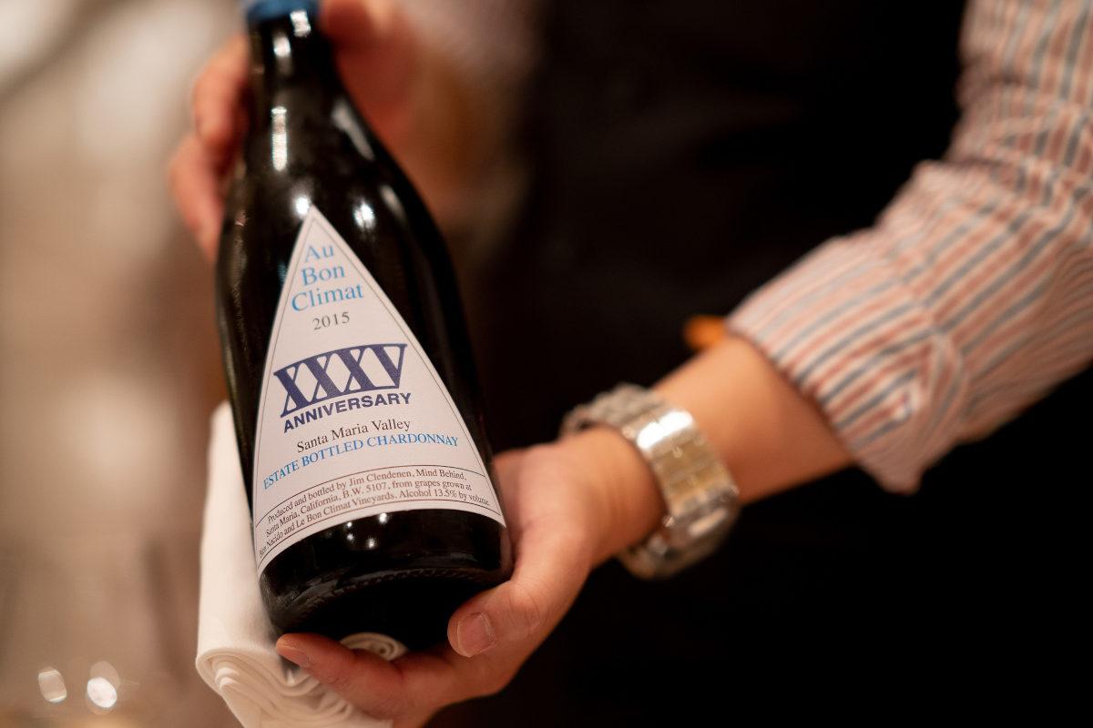 Slijterijmedewerker presenteert speciale wijn voor een jubileum