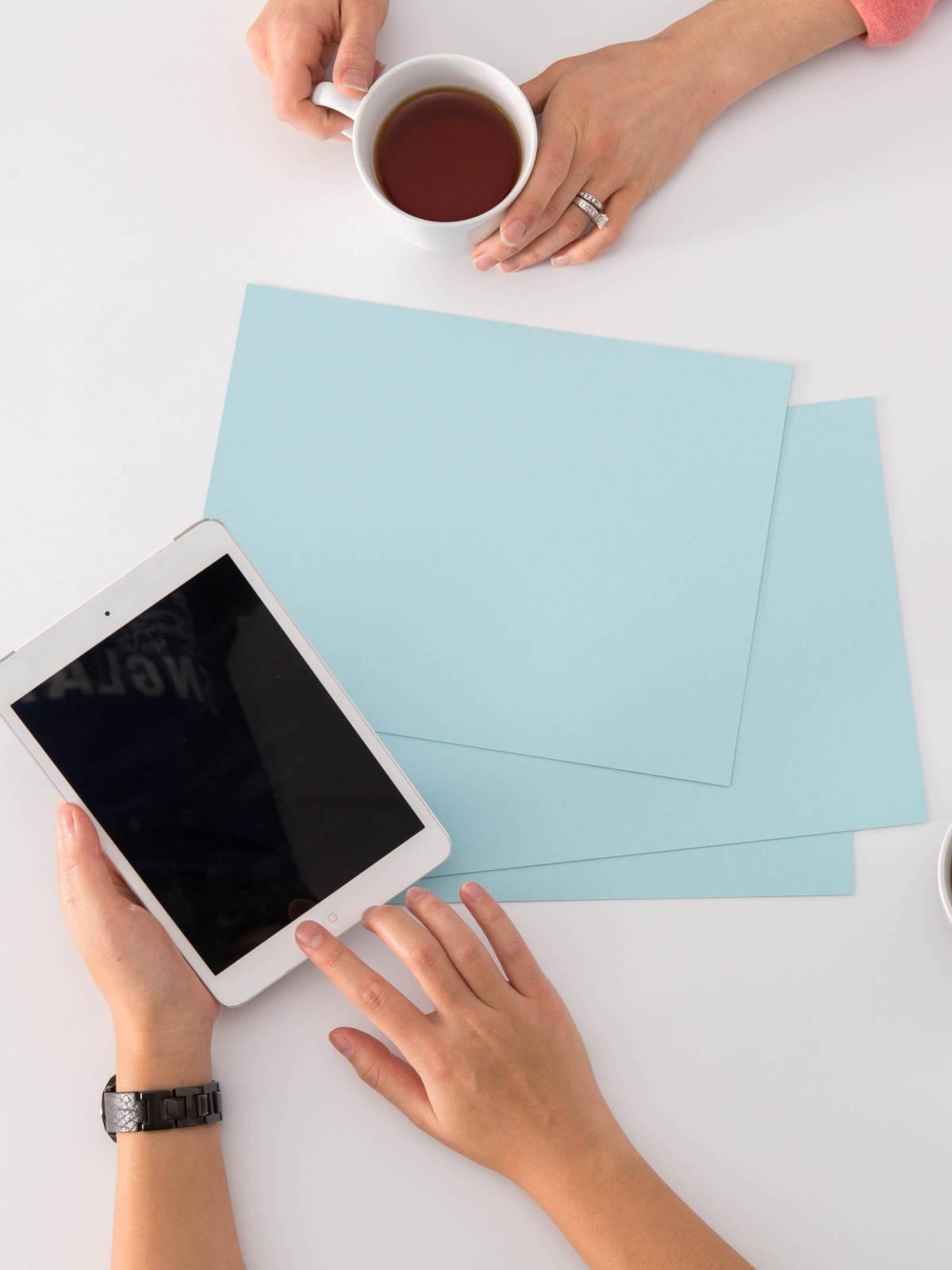Overleg tussen twee personen met tablet, papieren en warme drank