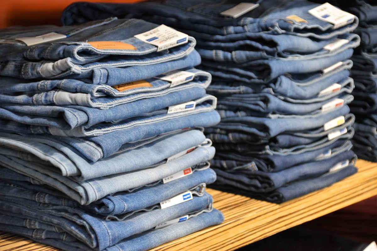 Stapels jeans met verschillende maten waarvoor je in het voorraadbeheersysteem maatbalken kunt gebruiken
