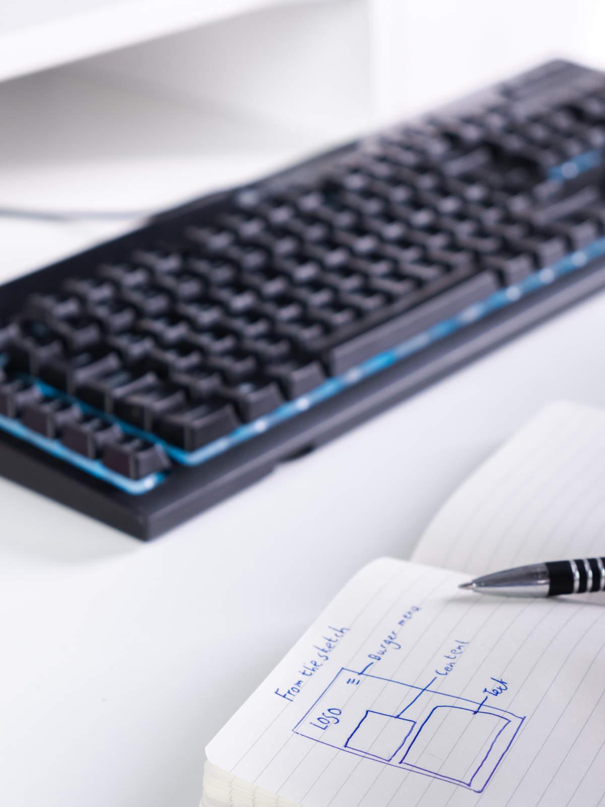 Blik op notitieboek met aantekeningen en pen, toetsenbord en onderkant computerscherm