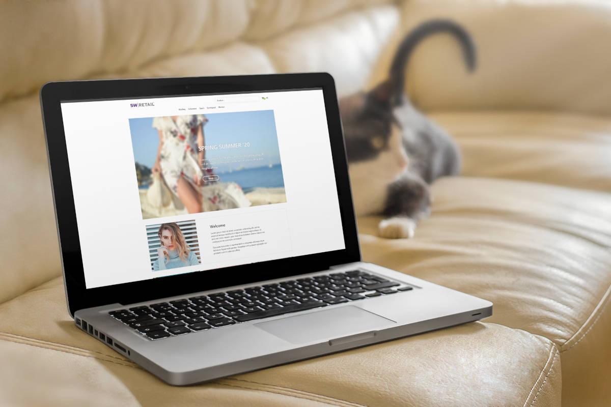 Voorbeeld SW-Retail webshop thema op een laptop die op een bank ligt met een kat ernaast
