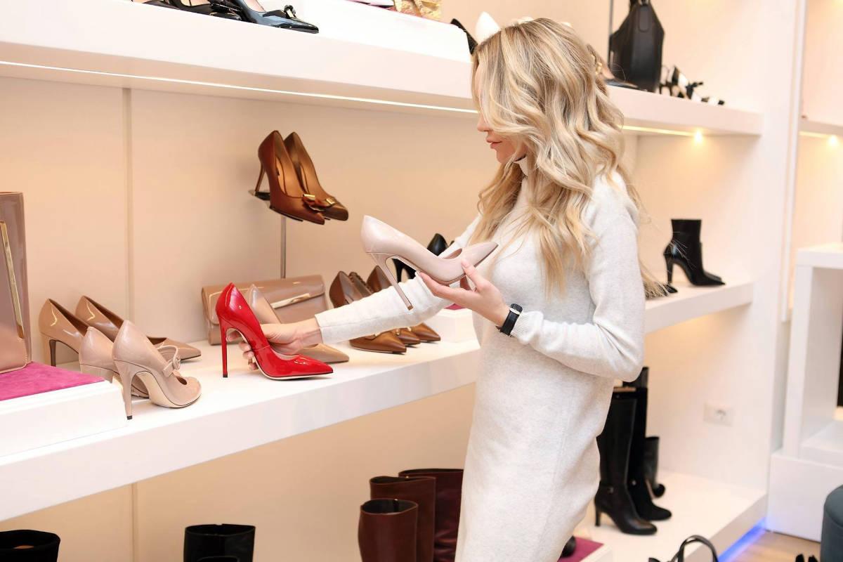 Medewerker in schoenenwinkel plaatst nieuwe schoenen op display